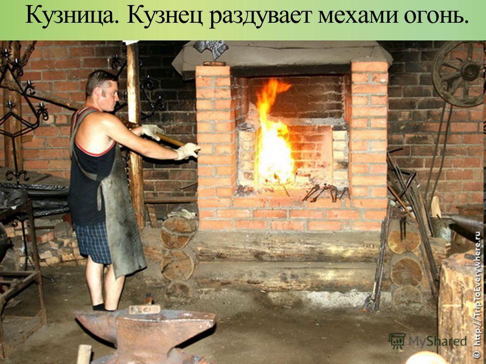 Кузница. Кузнец раздувает мехами огонь.
