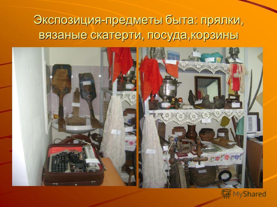 Экспозиция-предметы быта: прялки, вязаные скатерти, посуда,корзины