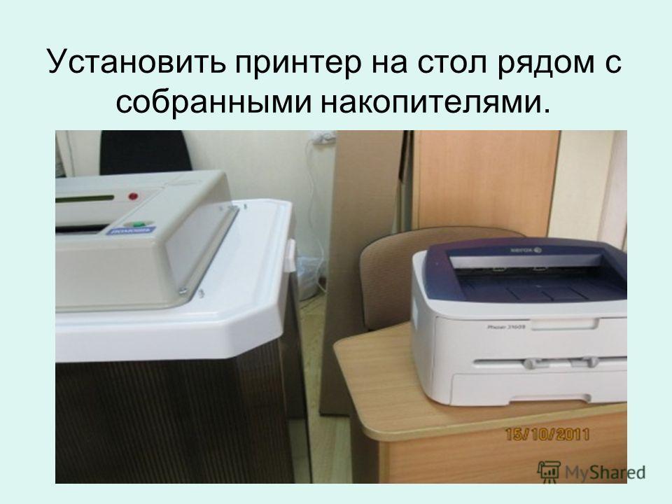 Установить принтер на стол рядом с собранными накопителями.
