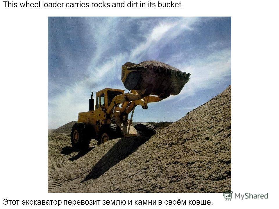 This wheel loader carries rocks and dirt in its bucket. Этот экскаватор перевозит землю и камни в своём ковше.