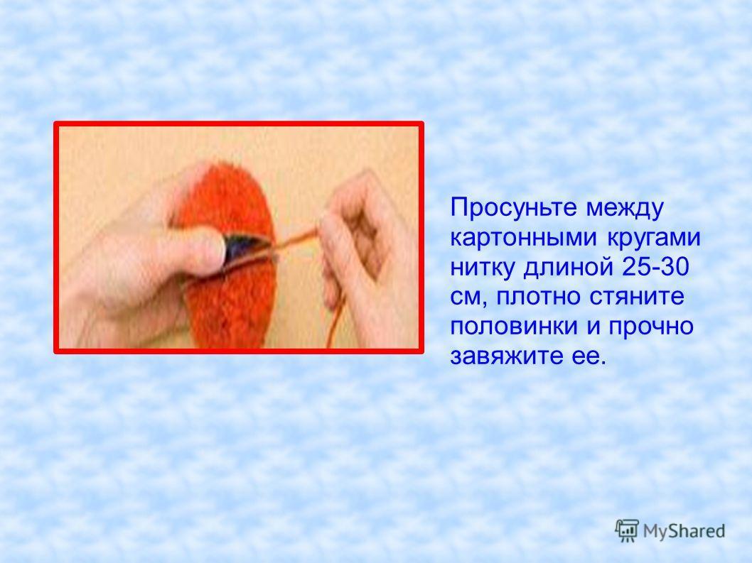 Просуньте между картонными кругами нитку длиной 25-30 см, плотно стяните половинки и прочно завяжите ее.