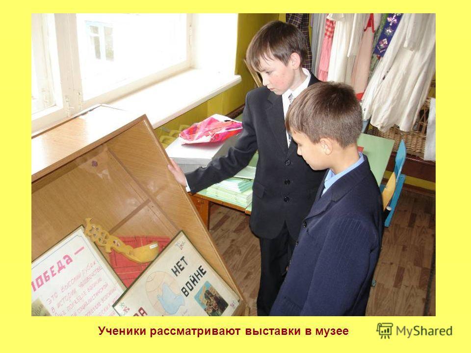 Ученики рассматривают выставки в музее