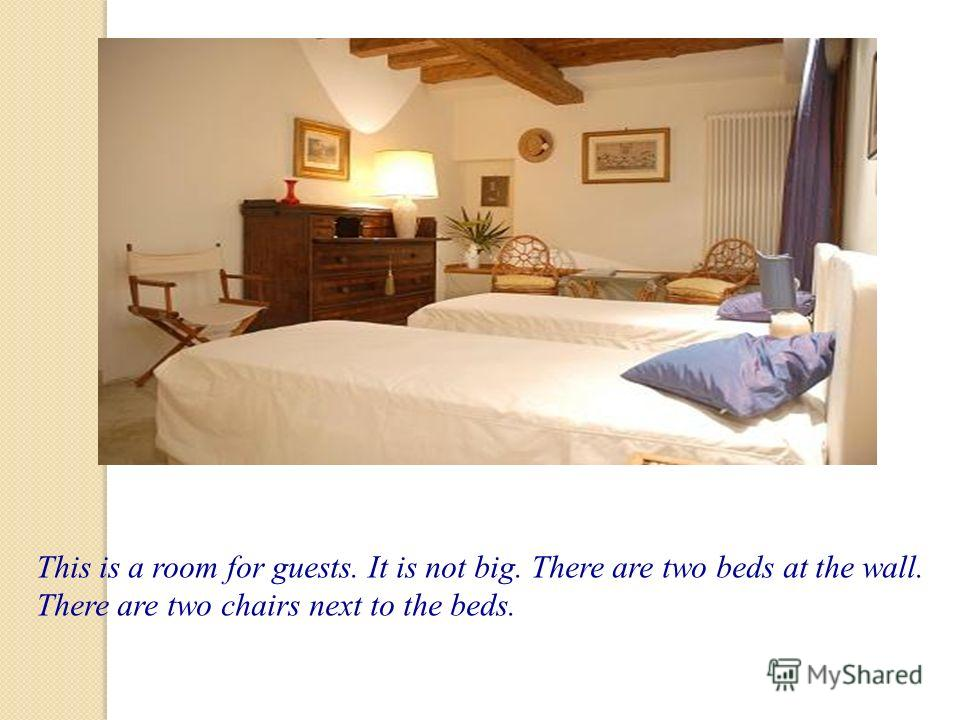 This is a room for guests. It is not big. There are two beds at the wall. There are two chairs next to the beds.