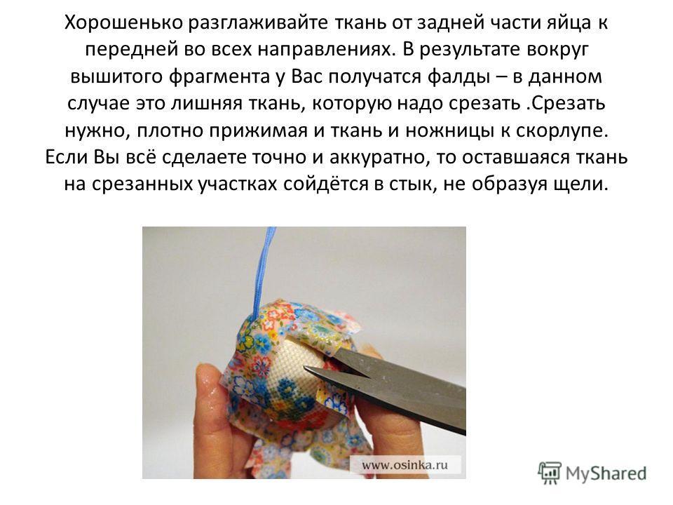 Хорошенько разглаживайте ткань от задней части яйца к передней во всех направлениях. В результате вокруг вышитого фрагмента у Вас получатся фалды – в данном случае это лишняя ткань, которую надо срезать.Срезать нужно, плотно прижимая и ткань и ножниц