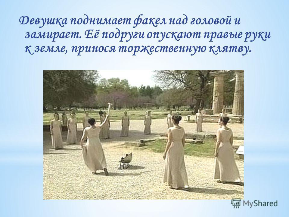 Девушка поднимает факел над головой и замирает. Её подруги опускают правые руки к земле, принося торжественную клятву.
