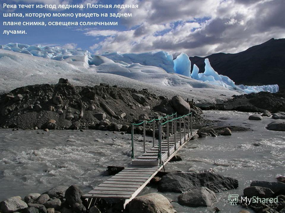 Река течет из-под ледника. Плотная ледяная шапка, которую можно увидеть на заднем плане снимка, освещена солнечными лучами.