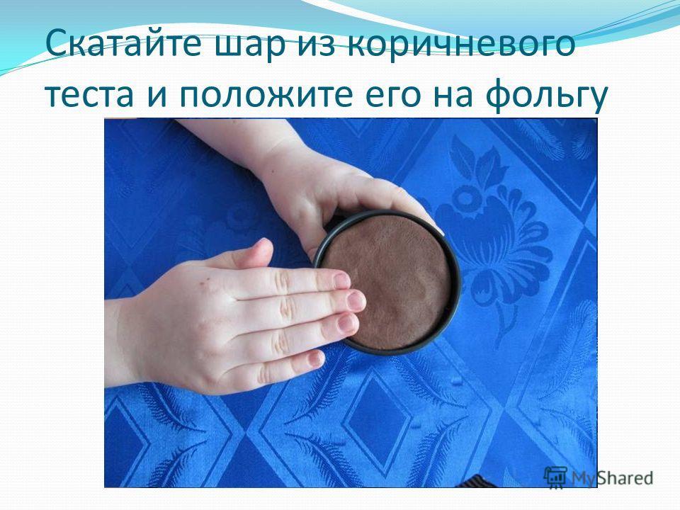 Скатайте шар из коричневого теста и положите его на фольгу