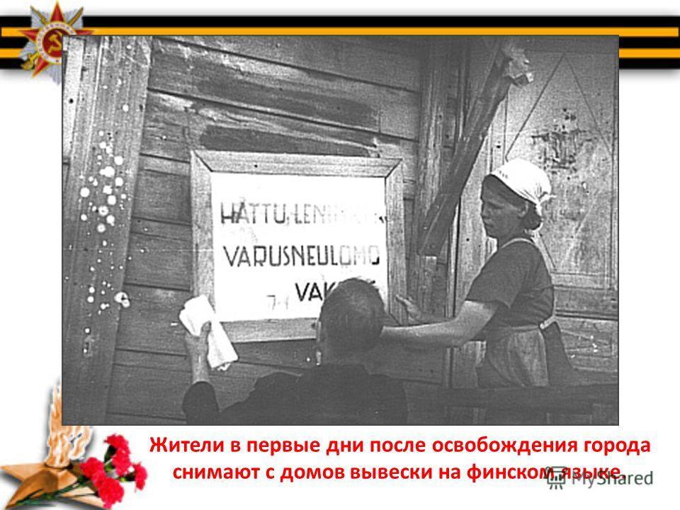 Жители в первые дни после освобождения города снимают с домов вывески на финском языке.