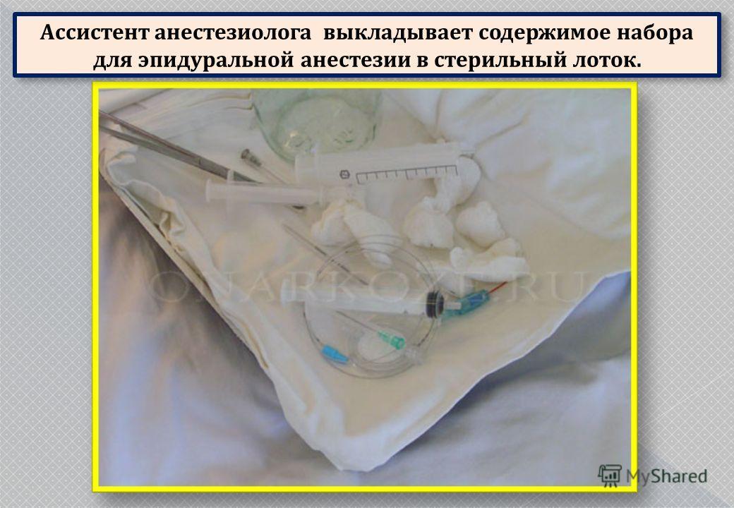 Ассистент анестезиолога выкладывает содержимое набора для эпидуральной анестезии в стерильный лоток.