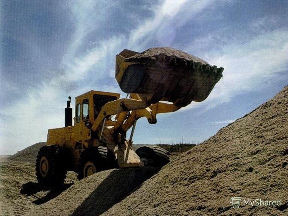 Этот экскаватор перевозит землю и камни в своём ковше.