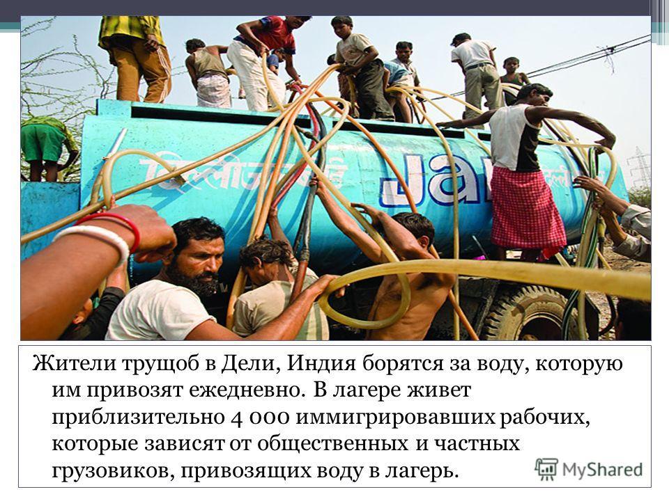 Жители трущоб в Дели, Индия борятся за воду, которую им привозят ежедневно. В лагере живет приблизительно 4 000 иммигрировавших рабочих, которые зависят от общественных и частных грузовиков, привозящих воду в лагерь.