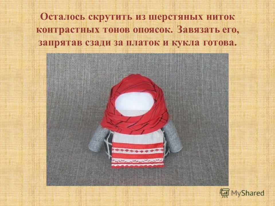 Осталось скрутить из шерстяных ниток контрастных тонов опоясок. Завязать его, запрятав сзади за платок и кукла готова.