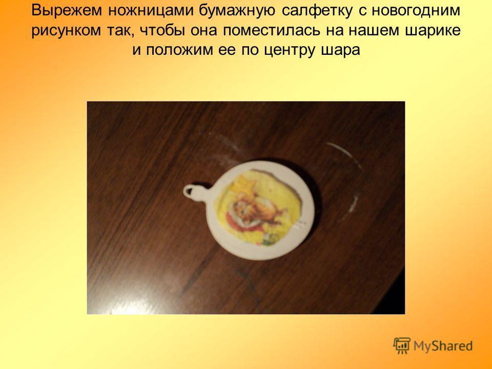 Вырежем ножницами бумажную салфетку с новогодним рисунком так, чтобы она поместилась на нашем шарике и положим ее по центру шара