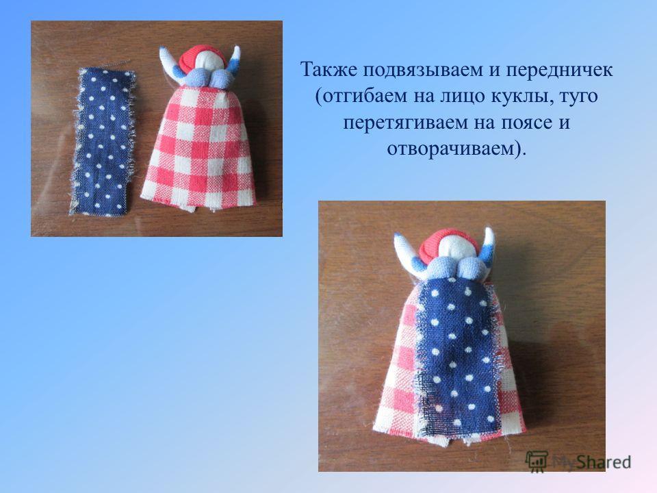 Также подвязываем и передничек (отгибаем на лицо куклы, туго перетягиваем на поясе и отворачиваем).