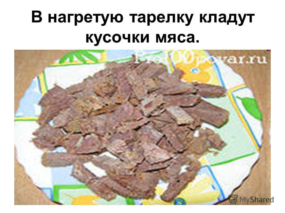 В нагретую тарелку кладут кусочки мяса.