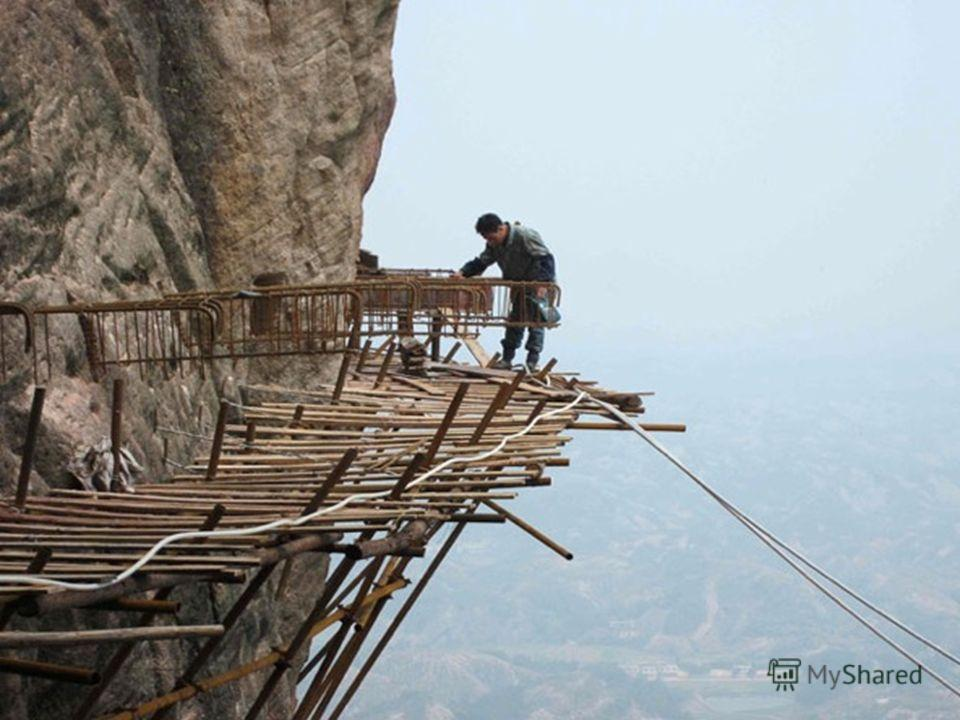 Thousands of metres up the vertiginous slopes of Shifou Mountain in Hunan Province, China, a team of workers, operating with hardly any safety measures, are building a footpath. На простирающихся вверх на тысячи метров головокружительных склонах горы