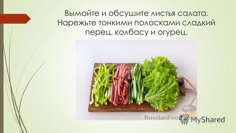 Вымойте и обсушите листья салата. Нарежьте тонкими полосками сладкий перец, колбасу и огурец.