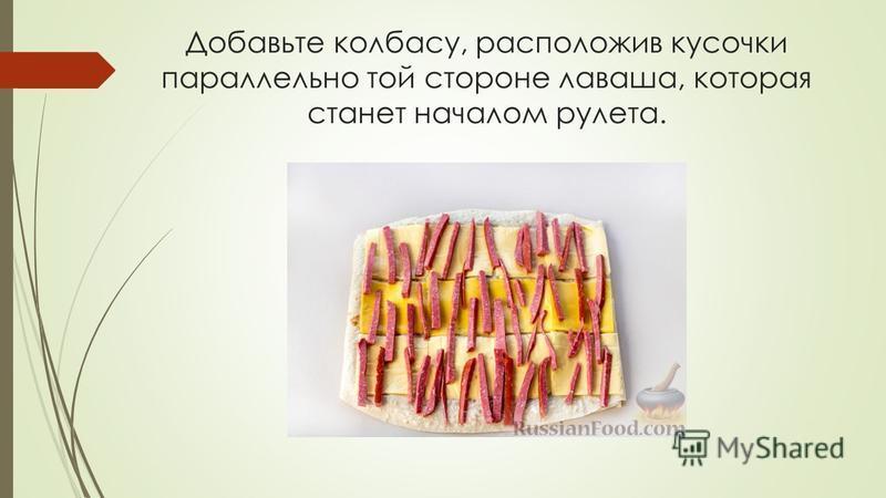Добавьте колбасу, расположив кусочки параллельно той стороне лаваша, которая станет началом рулета.